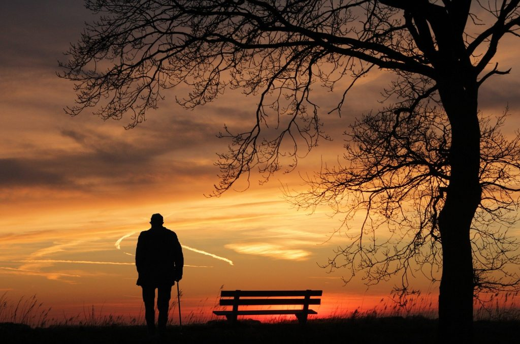 Lonely man in the distance at sunset illustrating social isolation